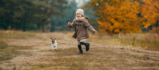 Child girl runs and plays with his dog during walk.