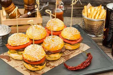 Homemade delicious mini hamburgers served with sauce and french fries. Homemade mini burgers.