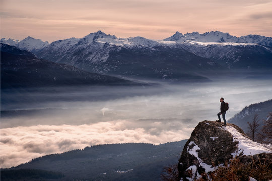 Man hiker looking mountain landscape with fog standing on a rock in Patagonia Argentina