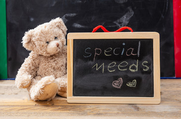 Teddy bear hiding behind a blackboard. Special needs text drawing on the blackboard