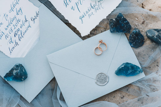 Wedding and engagement rings on an envelope next to invitation and menu