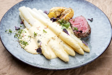 Modern barbecue dry aged sliced fillet steak with white asparagus in hollandaise sauce and roast potatoes as close up