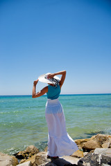 girl in a white hat and long dresss standing by the sea