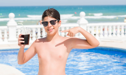 Young child drinking soda on holiday at the swimming pool by the beach very happy pointing with hand and finger