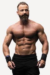 Hombre  con grandes músculos posando aislado sobre fondo blanco