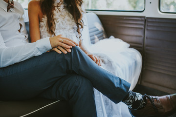Wedding couple holding hands in car
