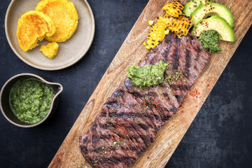 Barbecue dry aged wagyu flank steak with arepas corn, and chimichurri sauce as top view on a cutting board