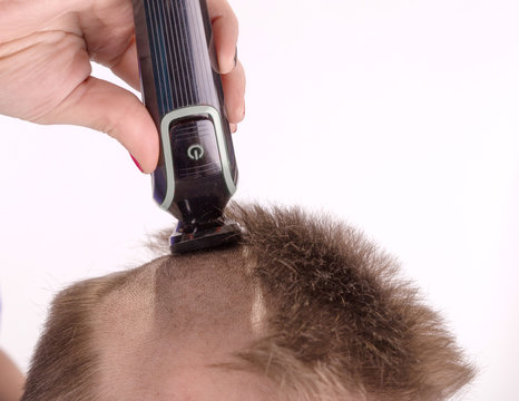 a woman's hand shaves her head with an electric thimble, an electric shaver
