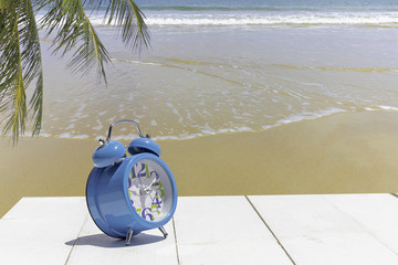 clock on wooden table at beach summer