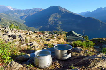 Boiling water outdoors in big aluminium cooking pots surrounded by a beautiful mountainous landscape at the small mountain village of Num, Nepal