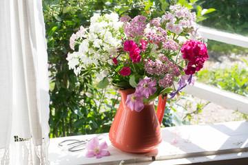 Bouquet of garden flowers on windowsill