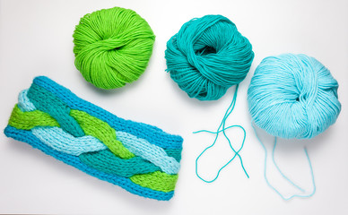 top view of colored yarn balls and knitting needles on white
