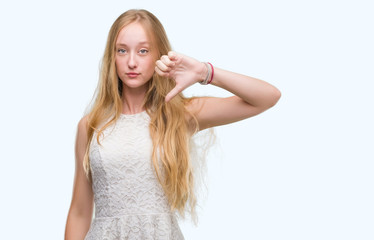 Blonde teenager woman with angry face, negative sign showing dislike with thumbs down, rejection concept