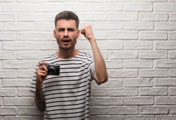 Young man holding vintage camera standing over white brick wall annoyed and frustrated shouting with anger, crazy and yelling with raised hand, anger concept