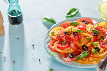 Homemade vegetarian tomato carpaccio salad in blue plate on blue background.