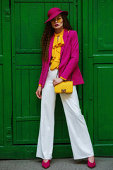 Outdoor full body portrait of young beautiful fashionable woman wearing trendy, colorful clothes, stylish accessories, posing near the green door. Female fashion concept