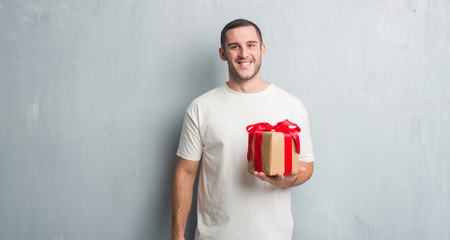 Young caucasian man over grey grunge wall holding a present with a happy face standing and smiling with a confident smile showing teeth