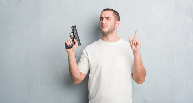 Young caucasian criminal man over grey grunge wall holding gun surprised with an idea or question pointing finger with happy face, number one