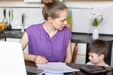 Busy female and young mother makes financial report, works with documents and modern laptop computer, has talk with her small son who feel bored, stands near table in kitchen. Motherhood concept