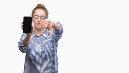 Young blonde woman using smartphone with angry face, negative sign showing dislike with thumbs down, rejection concept