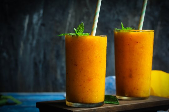 Mango Peach Punch or Smoothie on rustic background, selective focus