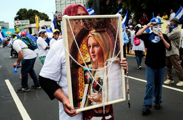 A demonstrator holds a picture of Virgin Mary during a march in support of the Catholic Church in Managua