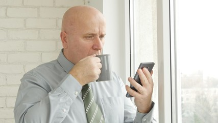 Businessman Read a Cellphone Text and Drink a Cup of Tea