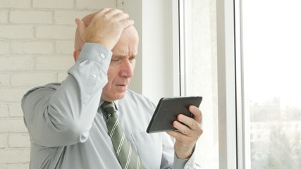 Businessman Image Reading Upset Financial News On Tablet and Gesturing Upset