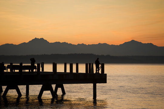 Sunset at Anchor Park in West Seattle, Washington. On a warm summer evening people flock to Alki Beach and Anchor Park for beautiful sunset views.