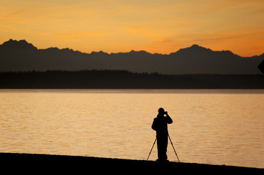 Photographing a Dramatic Sunset Over the Olympic Mountains, Seattle Washington. A photographer using a tripod on Alki Beach shoots the sun setting over the Olympic Mountains and Bainbridge Island.