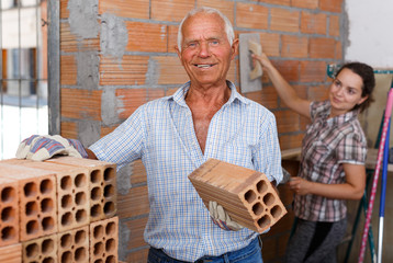 Man with daughter working with red brick