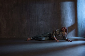 PTSD. Young woman lying on the floor, sadness and depression