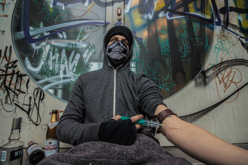 a drug addict  injects heroin into his arm and he is close to death