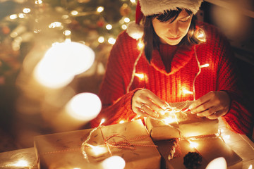 girl in santa hat and red sweater wrapping christmas presents in lights in evening festive room under tree illumination. kid opening modern craft gifts with candy cane. atmospheric moments
