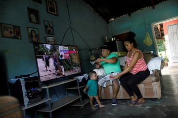 Rolando Bueso and his son Johan and Johan's mother pictured inside their house in La Libertad, in Comayagua state Honduras