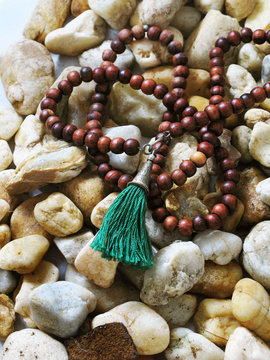 Wooden Buddha Beads laying on River Rocks