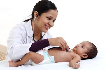 Cheerful female pediatrician holds newborn baby