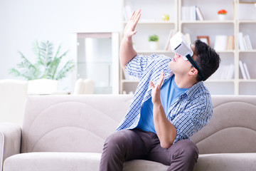 Man with virtual reality glasses playing at home