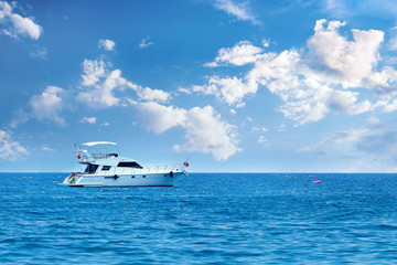 Large private motor yacht out on sea on blue sky background.Vacation holiday concept.