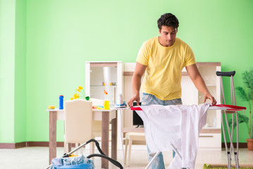 Leg injured man doing clothing ironing at home