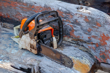 Orange gasoline engine portable chainsaw put on the old wooden plank