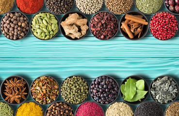 Fototapete - collection of Indian spices and herbs on teal table background.