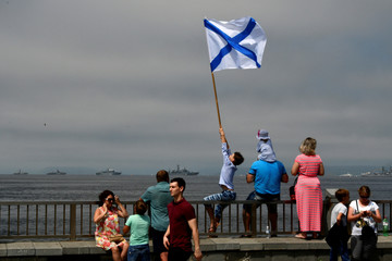 A boy flies Russian Navy flag during the Navy Day parade, in the far eastern city of Vladivostok