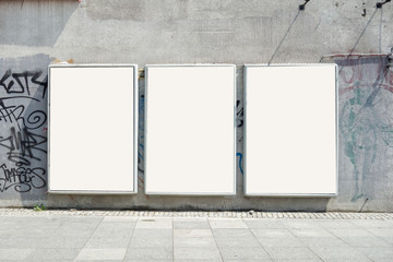 Thee empty advertising billboards on the wall of building