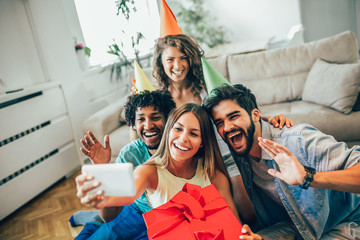 Happy friends or team with party accessories taking selfie and having fun