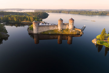 Olavinlinna fortress in the Kuusalmi strait on a July morning (aerial survey). Finland, Savonlinna