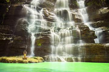 Young woman doing yoga in Cigangsa waterfall
