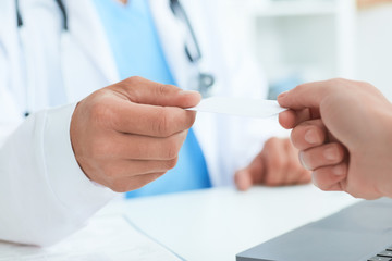 Male doctor's hand give white blank calling card to woman closeup in office. Physical, disease prevention, examine patient, instrument shop, healthy lifestyle, family doctor concept