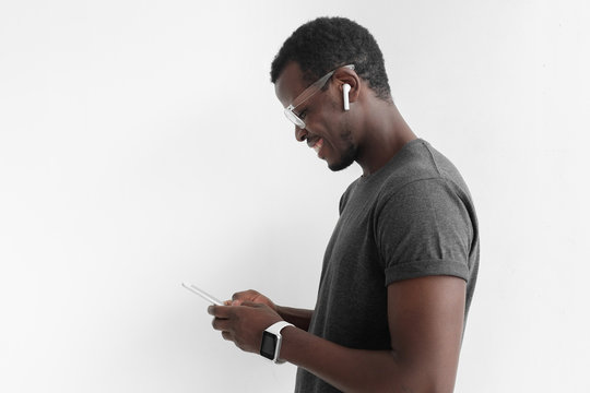 Side portrait of handsome African American man in gray t shirt, isolated on gray background, looking at screen of smartphone while exchanging messages or surfing Internet