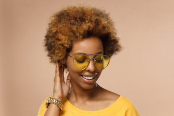 Horizontal closeup headshot of young smiling flirty dark skin african american woman in golden glasses, isolated on brown background, with turned head and touching her hair
